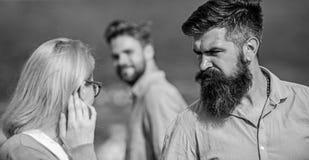 Echtgenoot die strikt op zijn vrouw letten bekijkend een andere kerel terwijl gang Voorbijganger die aan dame glimlachen Jaloers  stock foto