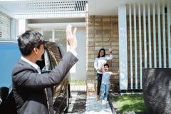 Echtgenoot die vaarwel aan zijn familie golven alvorens te gaan werken royalty-vrije stock foto's
