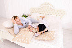 Echtgenoot die vrouw in bed vroeg in de ochtend in een witte ruimte koesteren Stock Foto