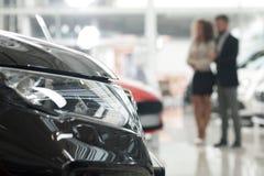 Echtgenoot en vrouw die auto in autotoonzaal waarnemen stock afbeeldingen