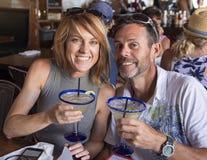 Echtgenoot en vrouw die Margaritas roosteren stock foto's