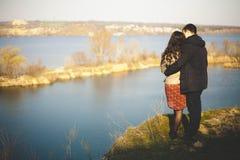 Echtgenoot en vrouw op de kust van het meer met rotsachtige kusten, de vroege lente Silhouetten van minnaars die in het water op  Stock Fotografie