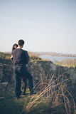 Echtgenoot en vrouw op de kust van het meer met rotsachtige kusten, de vroege lente Silhouetten van minnaars die in het water op  Royalty-vrije Stock Afbeelding