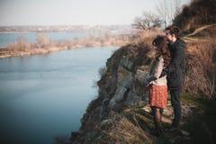 Echtgenoot en vrouw op de kust van het meer met rotsachtige kusten, de vroege lente Silhouetten van minnaars die in het water op  Royalty-vrije Stock Foto's