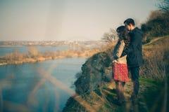 Echtgenoot en vrouw op de kust van het meer met rotsachtige kusten, de vroege lente Silhouetten van minnaars die in het water op  Stock Afbeelding