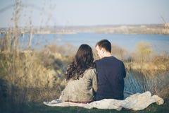 Echtgenoot en vrouw op de kust van het meer met rotsachtige kusten, de vroege lente Silhouetten van minnaars die in het water op  Stock Foto's