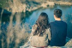 Echtgenoot en vrouw op de kust van het meer met rotsachtige kusten, de vroege lente Silhouetten van minnaars die in het water op  Royalty-vrije Stock Afbeeldingen