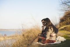 Echtgenoot en vrouw op de kust van het meer met rotsachtige kusten, de vroege lente Silhouetten van minnaars die in het water op  Stock Afbeeldingen