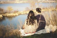 Echtgenoot en vrouw op de kust van het meer met rotsachtige kusten, de vroege lente Silhouetten van minnaars die in het water op  Royalty-vrije Stock Foto