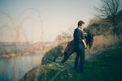 Echtgenoot en vrouw op de kust van het meer met rotsachtige kusten, de vroege lente Silhouetten van minnaars die in het water op  Royalty-vrije Stock Fotografie