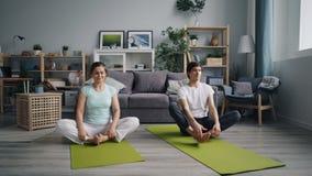 Echtgenoot en vrouwen het uitrekken zich lichaam en benen die thuis in vlinderpositie ontspannen stock video