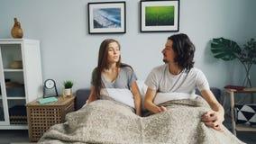 Echtgenoot en vrouwenontwaken die samen dan naar slaap opnieuw in bed gaan thuis stock videobeelden
