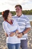 Echtgenoot en vrouwenpaar die gelukkig op het strand kijken Stock Foto's
