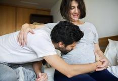 Echtgenoot het kussen babybuil van zwangere vrouw stock foto