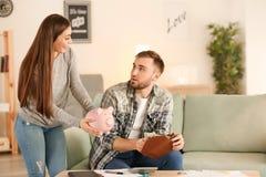 Echtgenoot met salaris en lastige vrouw met spaarvarken binnen De besparingenconcept van het geld stock fotografie