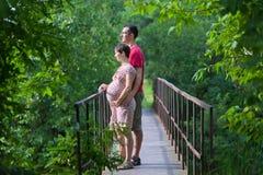 Echtgenoot met zijn zwangere vrouw op de brug Stock Afbeeldingen