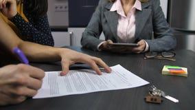 Echtgenoot` s handen die hypotheekcontract ondertekenen