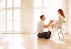 Echtgenootzitting op de vloer, zwangere vrouw op een stoel De echtgenoot bekijkt affectionately zijn vrouw stock afbeelding