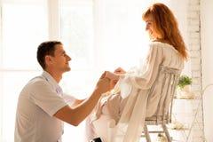 Echtgenootzitting op de vloer, zwangere vrouw op een stoel De echtgenoot bekijkt affectionately zijn vrouw royalty-vrije stock foto