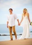 Echtpaar, bruid en bruidegomholdingshanden bij zonsondergang op beaut Royalty-vrije Stock Foto's
