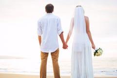 Echtpaar, bruid en bruidegomholdingshanden bij zonsondergang op beaut Stock Afbeeldingen