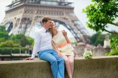 Echtpaar die enkel dichtbij de toren van Eiffel koesteren stock afbeeldingen