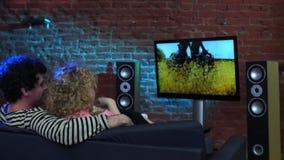 Echtpaar die op TV letten etend popcorn stock footage