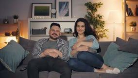Echtpaar die TV-op zitting op laag letten die binnenshuis het bekijken camera glimlachen stock footage
