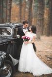 Echtpaar enkel in de luxe retro auto op hun huwelijksdag stock foto's