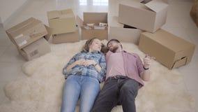 Echtpaarbewegingen in een nieuw huis Het kijken omhoog jong paar die op de vloer met vele dozen dichtbij liggen Jonge mensen stock footage