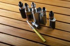 ecig的电子香烟mods在木背景 vape设备和香烟 库存图片