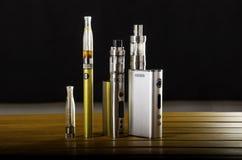 ecig的电子香烟mods在木背景 vape设备和香烟 免版税库存图片