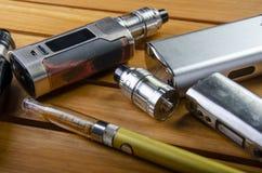 ecig的电子香烟mods在木背景 vape设备和香烟 免版税图库摄影