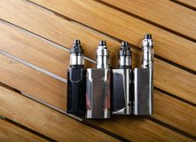 ecig的电子香烟mods在木背景 vape设备和香烟 免版税库存照片