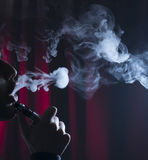Ecigarette или сигарета e с облаками на темной предпосылке стоковые фото