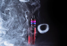 Ecigarette mod in smoke. And smoke ring stock photography