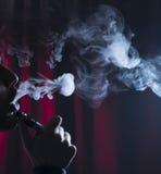 Ecigarette o cigarrillo de e con las nubes en un fondo oscuro Fotos de archivo