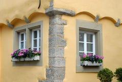 Ecke des bunten gelben Hauses mit zwei Fenstern und Blumen in der Stadt von Rothenburg in Deutschland Lizenzfreie Stockfotografie