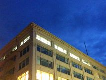 Ecke des typischen amerikanischen Bürogebäudes mit Verdunkelungsnächtlichen himmeln Lizenzfreies Stockfoto