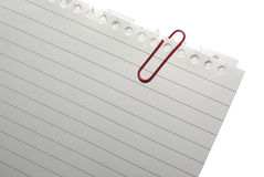 Ecke des unbelegten Anmerkungspapiers mit roter Papierklammer. Stockfoto