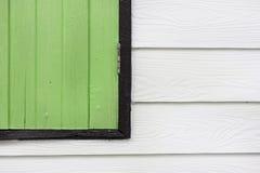 Ecke eines grünen hölzernen Fensters auf weißer hölzerner Wand in einem Haus Lizenzfreie Stockfotos