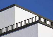 Ecke eines weißen Gebäudes mit diagonalem Balkongeländer und blauem Himmel stockfotos