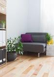Ecke eines Wohnzimmers mit grauem Lehnsessel und Anlagen Stockbild