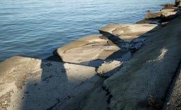 Eckige gebrochene Betonplatten am Rand von einem ruhigen Ozean bellen am späten Nachmittag Lizenzfreie Stockbilder