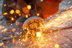 Eckige Schleifmaschine schneidet Metall mit Funken Stockfotografie