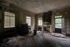 Eckzimmer mit Einrichtungsgegenständen u. Kamin - verlassene Villa Lizenzfreie Stockfotos