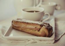Eclair шоколада на плите и кофе Стоковые Изображения