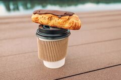 Free Eclair And Sweet Hot Coffee. Quick Takeaway Snack With A View Of The City Embankment In The Park Royalty Free Stock Photos - 191286508