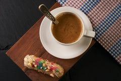 Eclair crémeux français et tasse de café chaude images stock