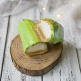 Eclair cut with tangerine jelly, orange mousse and mascarpone cream decorated with green icing and gold lace decoration. On wooden plate. The concept of stock photos